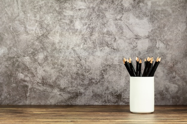 Many pencils in a white ceramic cup on old wooden desk in office