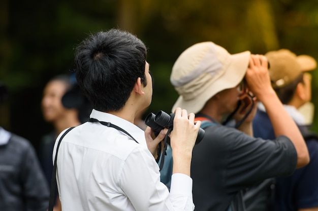 Many people are using cameras to shine something in the park.