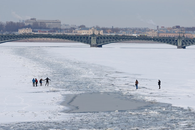 Many people crossing of frozen neva river in st. petersburg at early spring