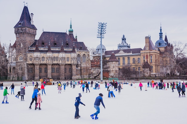 Many people spend their holidays skating in city park ice rink in budapestin front of vajdahunyad castle, hungary