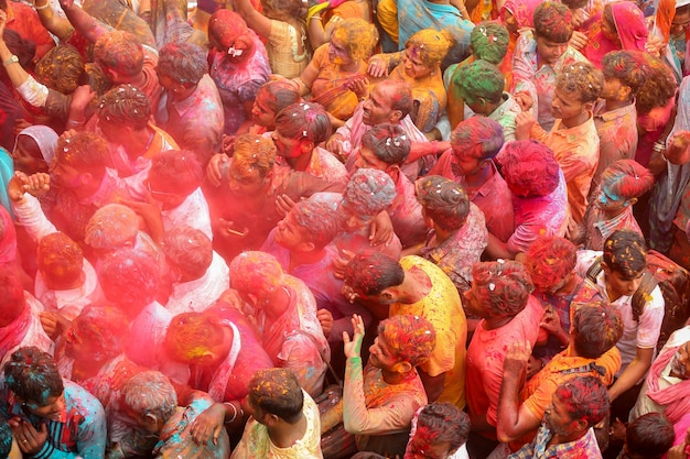 Many people throwing powder paint into the air holi festival premium photo