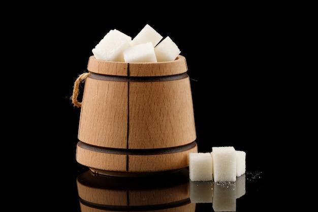 Много кусочков белого сахара в деревянной бочке