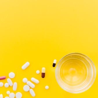 Многие таблетки и капсулы возле стакана воды на желтом фоне