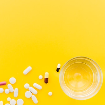 Many pill and capsules near the glass of water on yellow backdrop