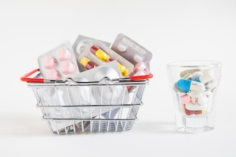 Many pills pack in the shopping cart and glass on white background