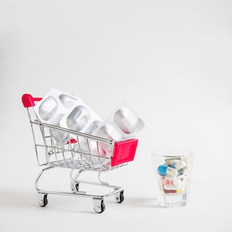 Many pills in the small glass with shopping cart with silver blister pills on white background