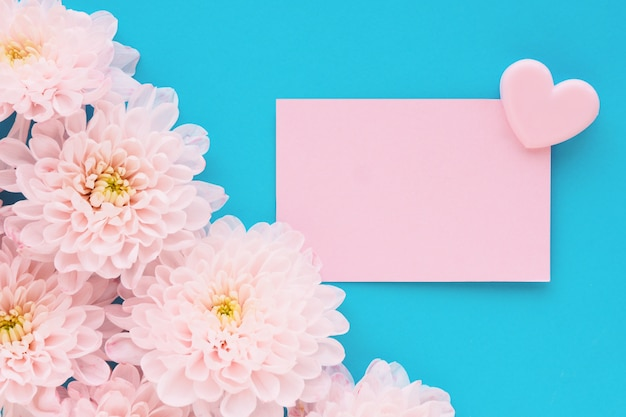 Many pink chrysanthemum flowers with a yellow center and a rectangular sticker with a heart clip on a blue table.