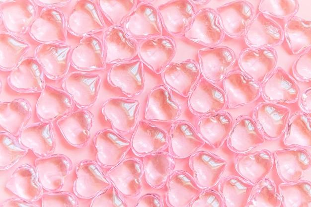 ピンクのパステル背景、結婚式のロマンスのシンボルに分離された多くのピンクの心