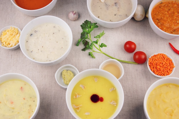 Many plates with different soups on the table.