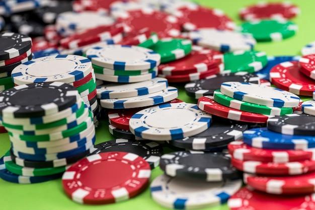 緑の背景に分離された多くのポーカーチップ