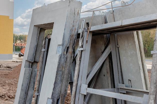 많은 프리캐스트 콘크리트 벽 패널이 건설 현장에서 설치를 기다리는 보관 구역에 보관되어 있습니다.