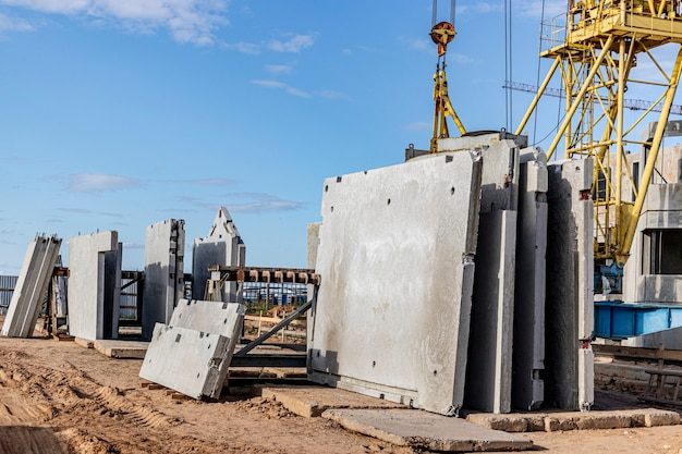 Many precast concrete wall panels are stocking in the storage area waiting for installation at construction site.