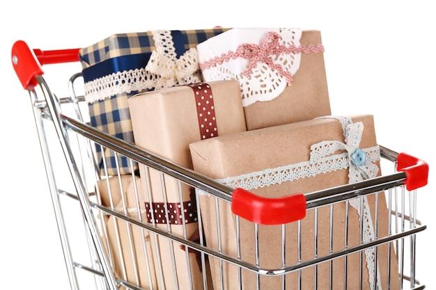 白い表面に隔離されたショッピングカートの多くのプレゼントボックス
