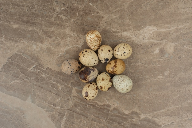 Many of quail eggs on marble background .