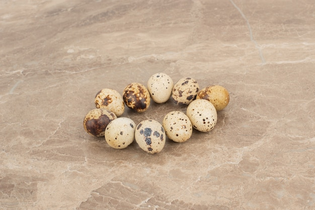 Molte delle uova di quaglia sul tavolo di marmo.