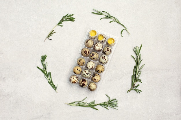 Many quail eggs in plastic packaging on stone background