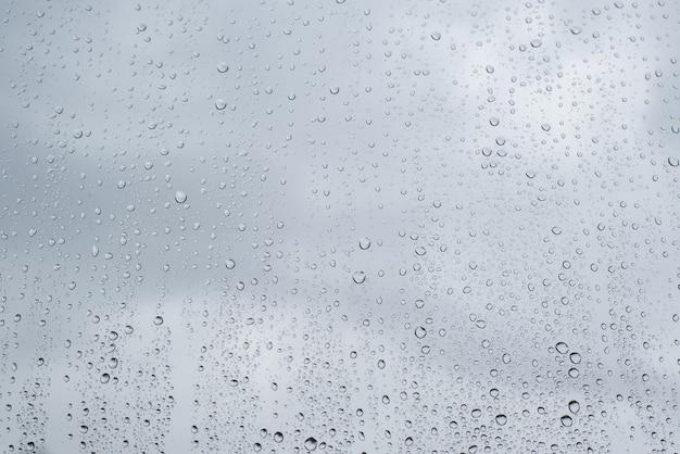窓にたくさんの雨滴、クローズアップの背景。雨の悪天候。
