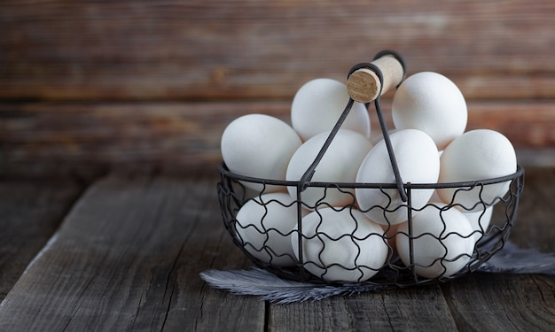 木製の素朴な背景にヴィンテージの金属のバスケットで多くの生の白い有機卵