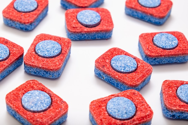 Many red and blue dishwasher soap tablets on white background, kitchen equipment and solutions for washing dishes