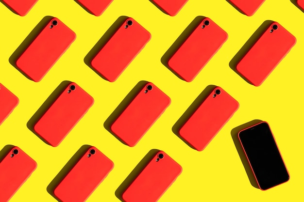 Many red cell phones on yellow background communication and gadgets bright pattern