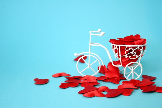 Многие красные сердечки приводят в движение белый декоративный велосипед из проволоки. синий фон. концепция дня святого валентина. идея любви.