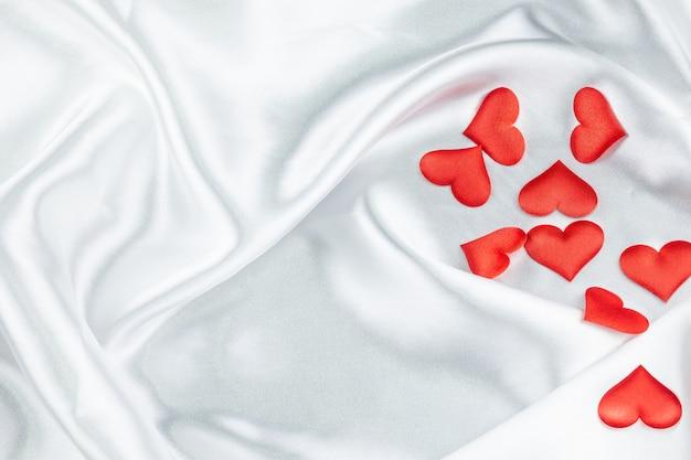 しわの白い毛布に多くの赤いハート