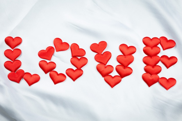 多くの赤いハートはしわのある白い毛布に愛という言葉を印刷します