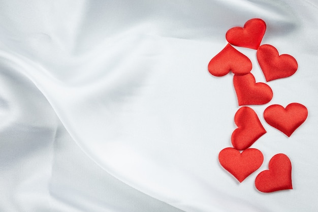 Many red hearts on a wrinkled on white blanket