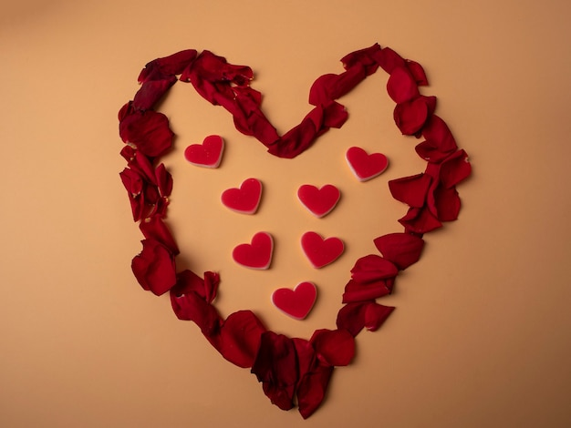 Many red petals from roses lie in the shape of a large red heart and in the center there are seven hearts on background