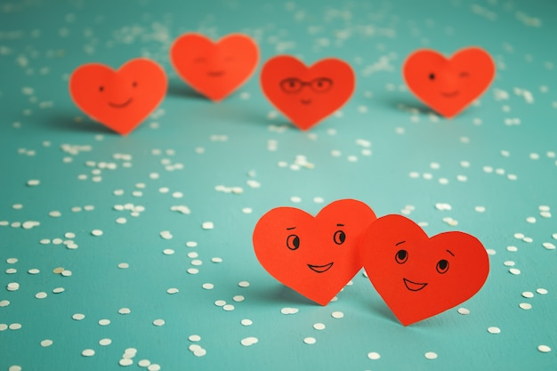 Many red smiling hearts on a blue table. st. valentine's day. couple in love.