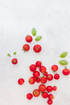 Many red tomatoes with basil leaves on textured background