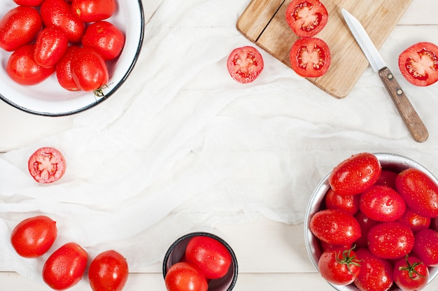 Many ripe red tomatoes on the white wooden table