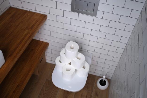トイレのトイレに白い紙のロールがたくさんあります