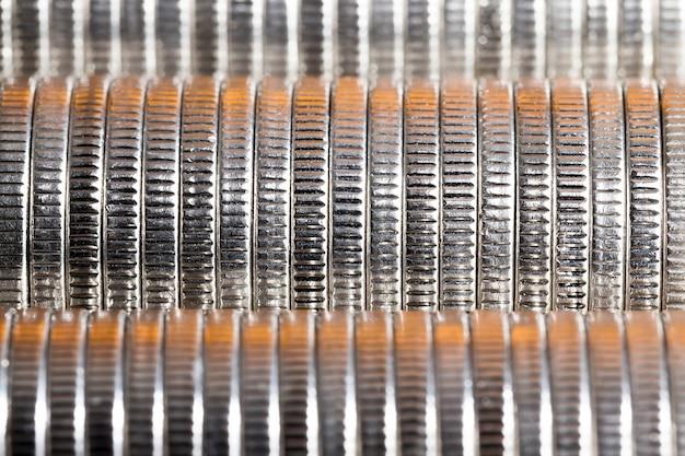 Многие круглые металлические монеты серебряного цвета с красной подсветкой, законное платежное средство, которое используется для платежей в штате, красивые монеты крупным планом с красным оттенком той же стоимости монеты