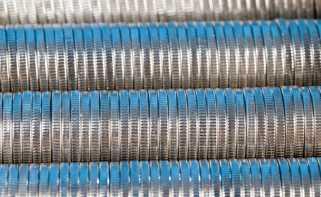 Many round metal coins of silver color illuminated in blue