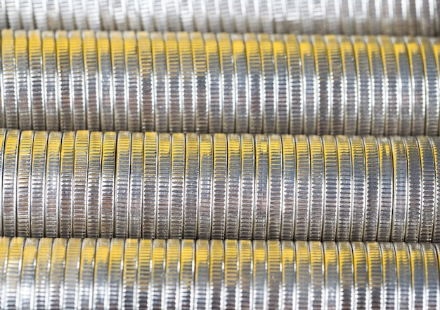 Many round metal coins of silver color illuminated in yellow, legal tender that is used for payments in the state, beautiful coins close-up with a yellow hue the same coin value
