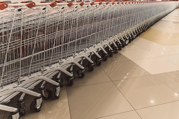 駐車場の近くのクローズアップと店の外の赤いショッピングカートの多くの列