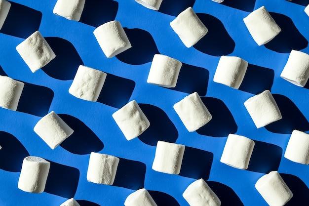 白いマシュマロの円筒形の列の多くは、青い背景の上にあります。不健康なジャンキーフードのパターン。お菓子のパターン