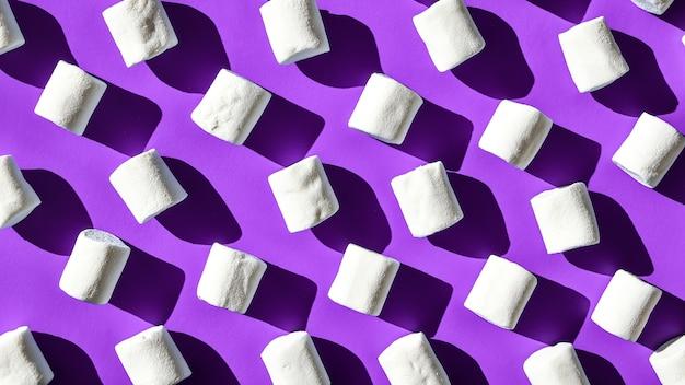 白いマシュマロの円筒形の列の多くは、紫色の背景にあります。不健康なジャンキーフードのパターン。お菓子のパターン