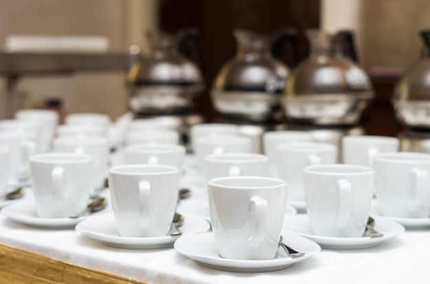Many rows of white coffee cup with saucer and teaspoon on table and coffee maker