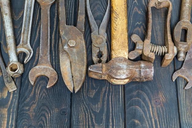 검은색 빈티지 나무 판자 작업 후 쌓인 많은 녹슨 오래된 도구