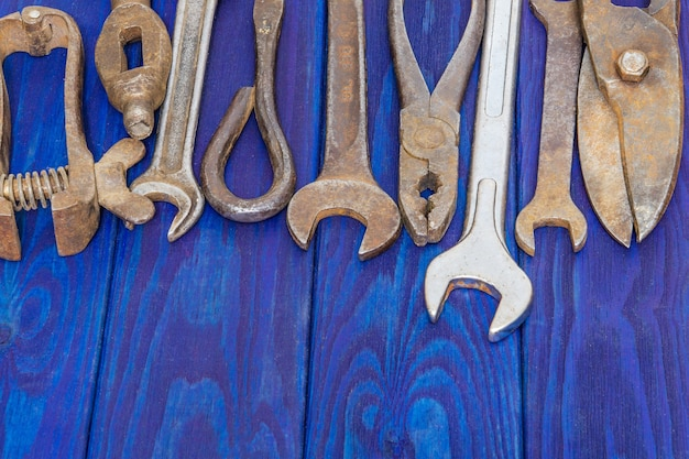 파란색 빈티지 나무 판자 세로 방향 작업 후 쌓인 많은 녹슨 오래된 도구