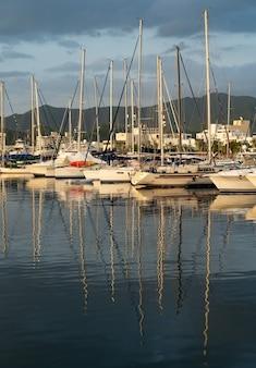 Многие парусники пришвартованы в пристани для яхт на фоне драматического восхода солнца с горами