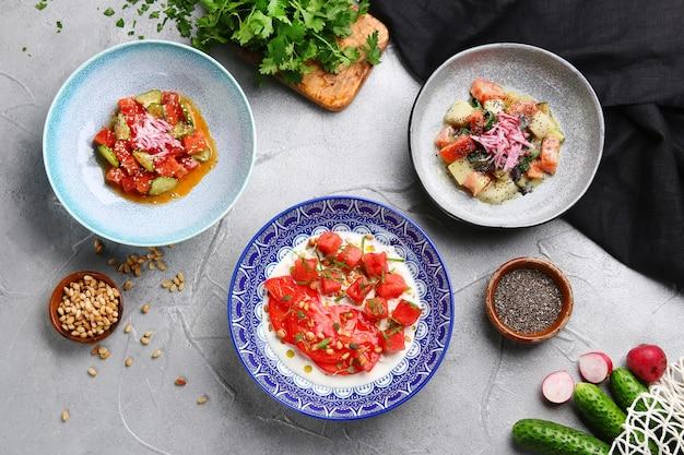 가벼운 콘크리트 테이블 위에 많은 샐러드가 경쟁합니다. 참치, 연어, 스트라 치아 텔라, 토마토와 수 말론 샐러드를 곁들인 세비체.