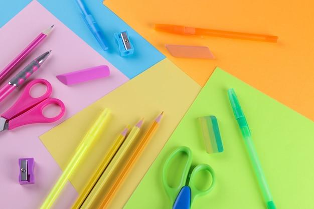 Многие школьные принадлежности на ярком разноцветном фоне
