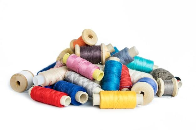 Многие швейные нитки разных цветов на белом фоне