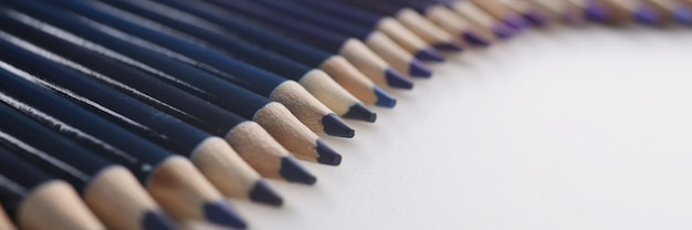 Many shades of wooden blue pencils lying on white background closeup