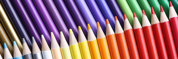 Many sharp wooden multicolored pencils background closeup