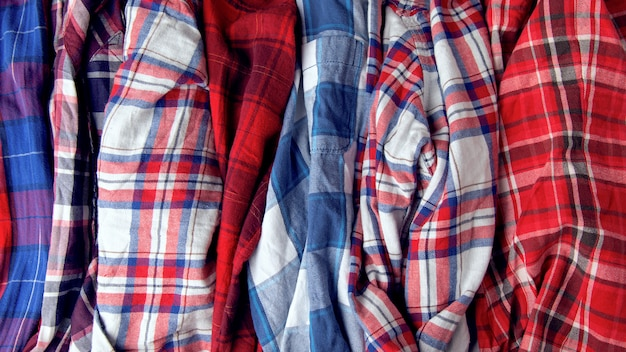 Many shirts plaid. a pile of clothes