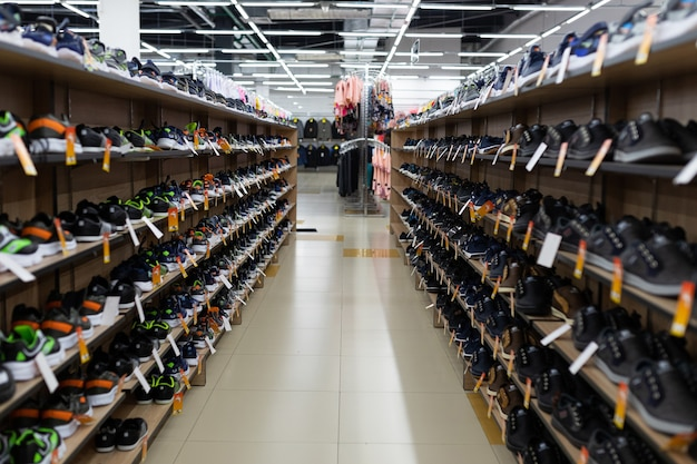 Many shoes on the shelves are in the shoe store